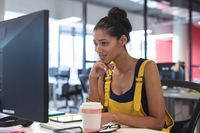 Mixed race female creative worker sitting at desk using computer