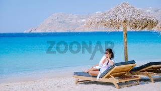 young girlon the beach of Mykonos, Elia beach Mikonos, Mykonos beach during summer with umbrella and luxury beach chairs beds, blue ocean at Elia beach Mikonos Greece