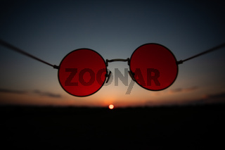 Summer sunset through the sunglasses with red lenses