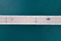 Aerial view of bridge road with cars over lake or sea.