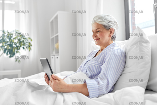 senior woman with tablet pc in bed at home bedroom