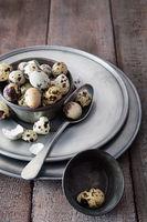 Quail eggs in tin bowl on wood table
