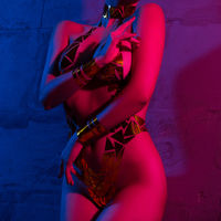 Nude woman with gold tape body art against wall
