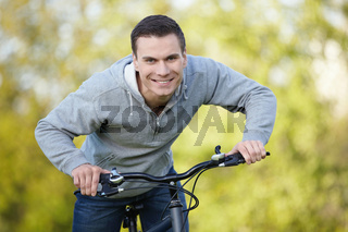 Young attractive man riding his bicycle in the park
