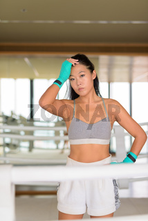 Asian woman kick boxer ready for exercise at gym boxing ring
