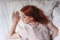 young woman in bed sleeping on stomach with head on pillow