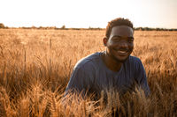 Handsome positive young man in grain field
