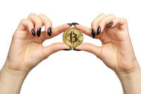 Female hands with black nails manicure and golden bitcoin in fingers. Isolated on white background.