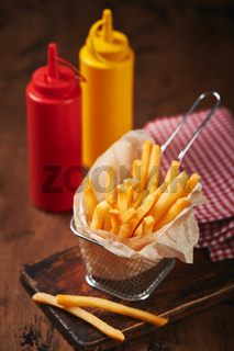 French fries in a metal mesh basket on a wooden board. Fast food concept, american food