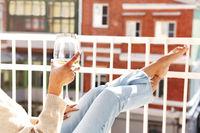 Unrecognizable woman enjoying wine on balcony
