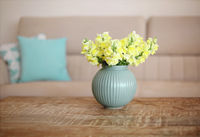 Wooden coffee table with bouquet of yellow flowers in vase on foreground in living room interior