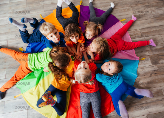 Cheerful children playing team building games on a floor