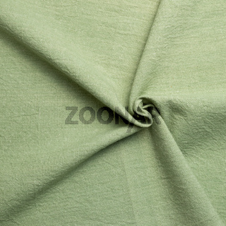 Crumpled natural green fabric texture background