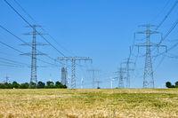 Strommasten und Stromleitungen mit Windrädern