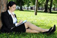 Businesswoman writing something to diary