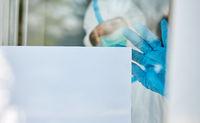 Klinikpersonal befestigt Aushang an Klinik Tür wegen Coronavirus