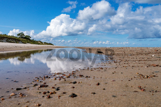 Reflection of clouds in the water. Beautiful sky. The sea coast. Deserted seashore.