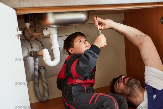 Sohn hilft Vater als Heimwerker bei Installation von Spüle