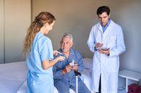 Ärzteteam und Senior Patient bei der Behandlung