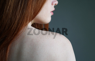 young woman showing bare shoulder with freckles on skin