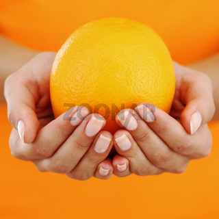 orange in woman hands close up