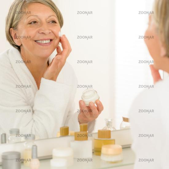 Senior woman apply anti-wrinkles cream look mirror