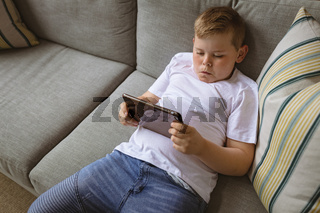 Caucasian boy using digital tablet sitting on the couch at home
