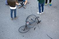 Bicycle accident on the road. Scene of cyclist and bicycle on the asphalt surrounded by people after being hit by a vehicle