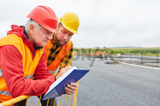 Zwei Bauarbeiter als Straßenbauer mit Checkliste