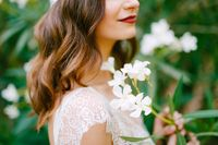 The bride stands by a blooming white oleander and holds a sprig of oleander in her hands, close-up