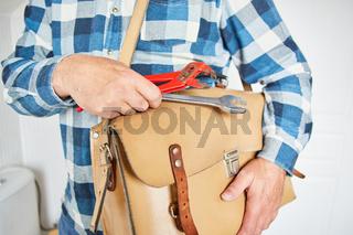 Klempner vom Notdienst mit Ledertasche und Werkzeug