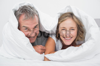Happy middle aged couple under the duvet