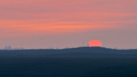 View of the skyline of Berlin, Germany in sunrise seen from lookout platform Wietkiekenberg on the lake Schwielowsee over vast forest area