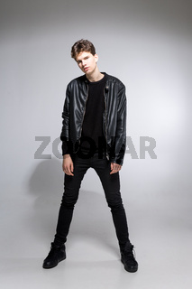 Full body image of model appearance of young fashionable guy in leather jacket and all black clothes posing on white background in studio. Handsome teenager in a black jacket studio shot