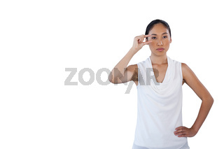 Businesswoman looking away while adjusting invisible eyeglasses