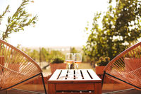 Glasses of white wine on rustic wooden table and flower pots on terrace outside