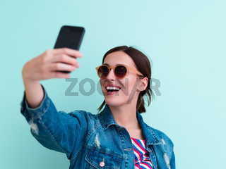 Portrait of young girl taking selfie on blue background