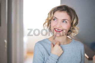 Beautiful blonde woman with curly hair is doing thinking posing. Positive emotion.