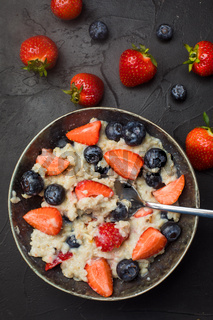 The concept of a healthy breakfast of oatmeal with strawberries and blueberries