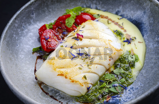 Modern style traditional fried skrei cod fish filet with mashed potato cream and coriander lime relish served as close-up on Nordic design plate with copy space