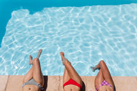Diverse group of female friends sunbathing by pool on a sunny day