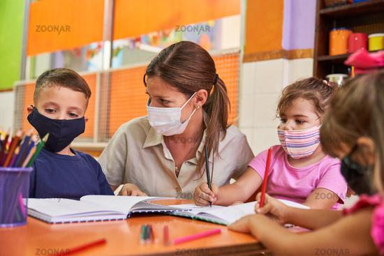 Lehrerin gibt Nachhilfe in der Schule für Kinder mit Maske