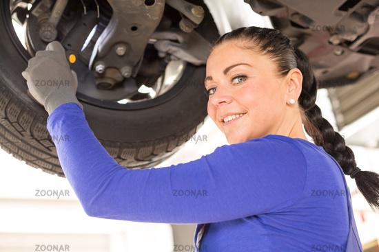 Kfz Mechanikerin repariert Fahrzeug auf Hebebühne