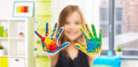 smiling girl showing painted hands at home