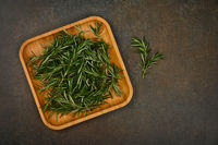 Fresh rosemary on bamboo wooden plate