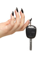 A female hand with a black nails manicure holds a black car key with her fingers. Isolated on white background.