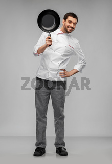 happy smiling male chef in jacket with frying pan