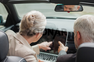Business people working together on laptop in classy cabriolet