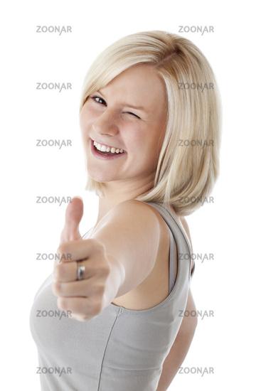Attraktive blonde Frau hält zwinkernd Daumen nach oben