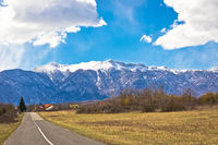 Lika road landscape and Velebit mountain snowy peaks view